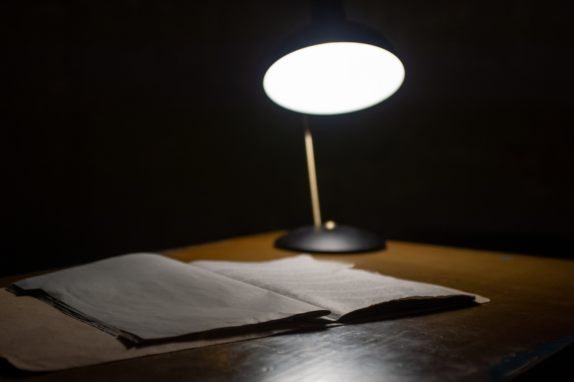 A file on a table in a dark room with a lamp shining on it
