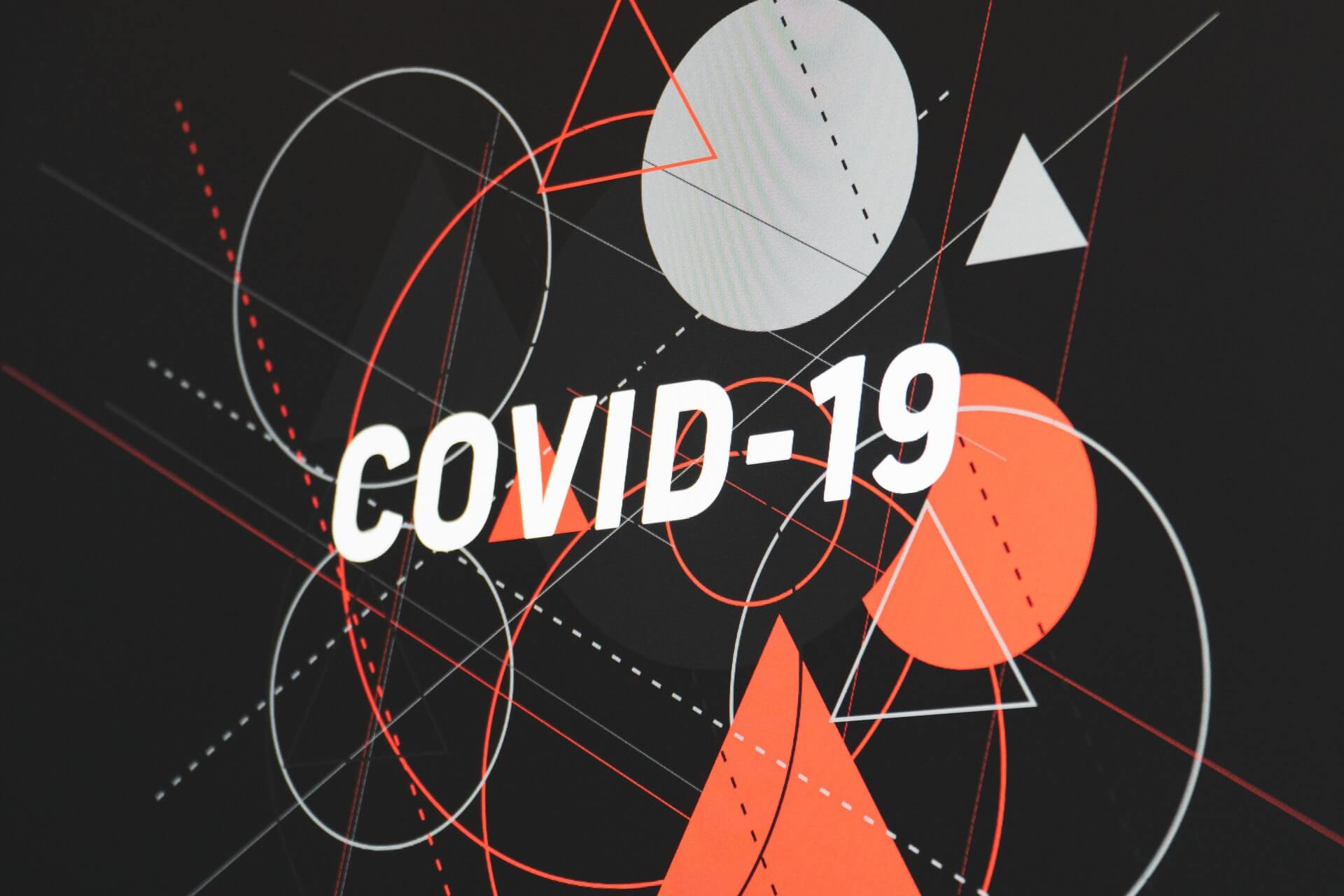 COVID-19 written on a background covered in shapes