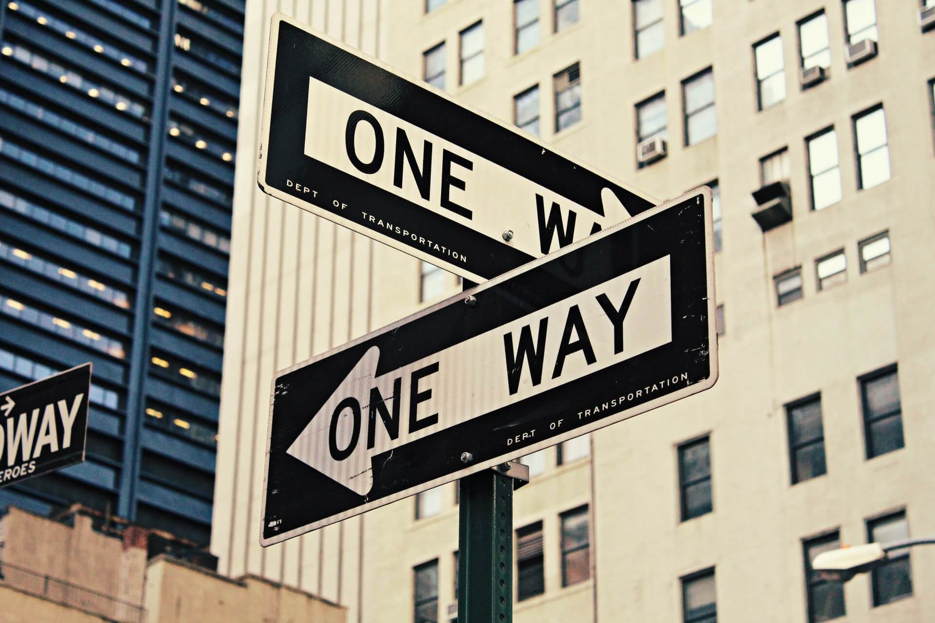 2 one way signs at a cross road