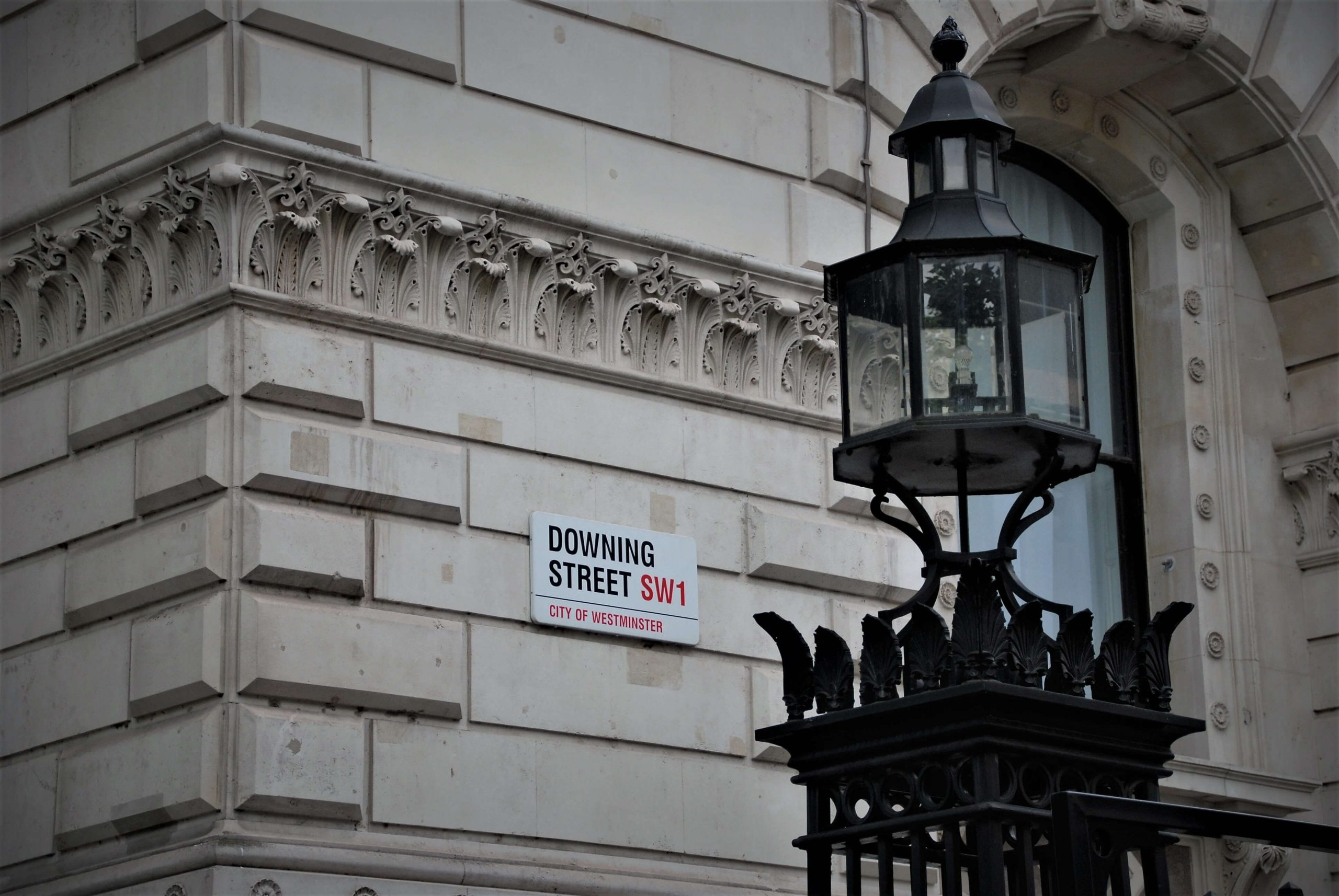 Downing Street sign with a lamp post in front of it